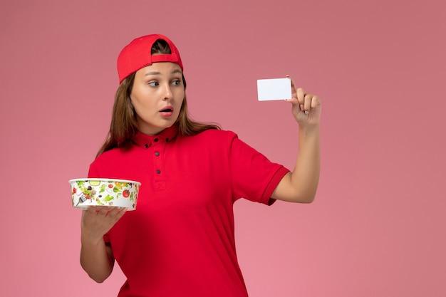 Vue de face femme courrier en uniforme rouge et cape tenant le bol et la carte de livraison sur le mur rose, service de livraison uniforme