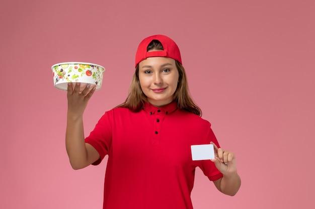 Vue de face femme courrier en uniforme rouge et cape tenant le bol et la carte de livraison sur le mur rose, travail de service de livraison uniforme