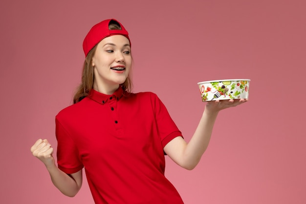 Vue de face femme courrier en uniforme rouge et cape tenant le bol de livraison acclamant le mur rose clair, livraison uniforme de service de travail