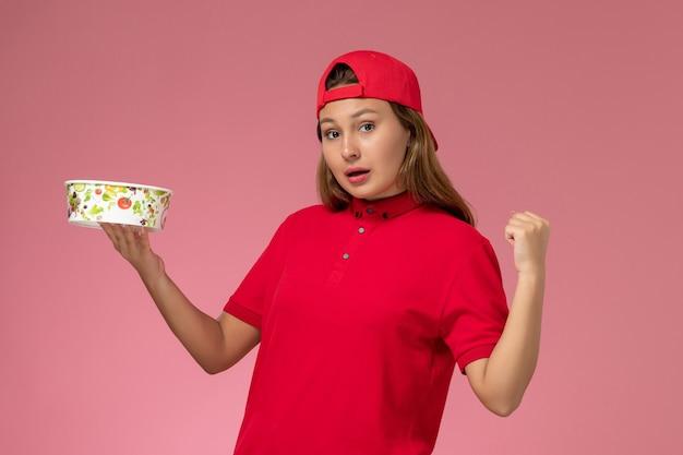 Vue de face femme courrier en uniforme rouge et cape tenant le bol de livraison applaudissant sur le mur rose, service de livraison uniforme