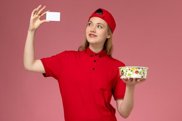 Vue de face femme courrier en uniforme rouge et cape tenant le bol de livraison avec carte sur le mur rose clair, livraison uniforme de service des travailleurs