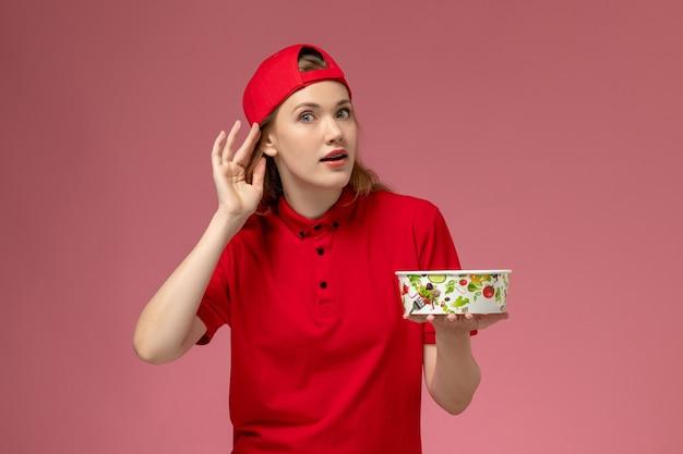 Vue de face femme courrier en uniforme rouge et cape tenant le bol de livraison essayant d'entendre sur le mur rose clair, service de livraison uniforme
