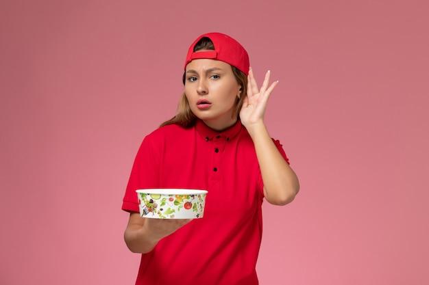 Vue de face femme courrier en uniforme rouge et cape tenant le bol de livraison essayant d'entendre sur le mur rose, service de livraison uniforme