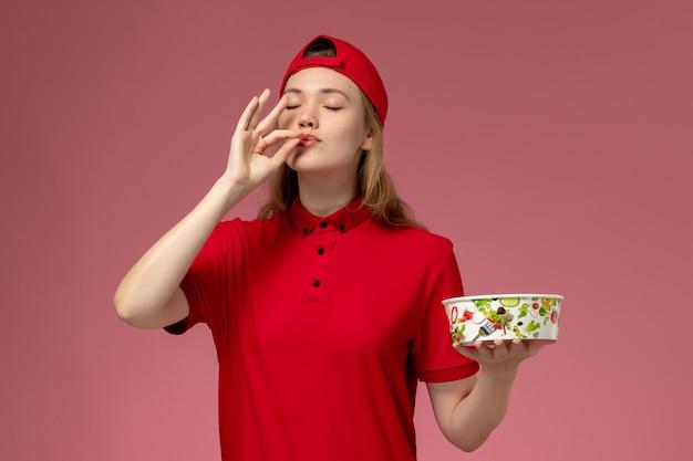 Vue de face femme courrier en uniforme rouge et cape tenant le bol de livraison sur le mur rose clair, livraison uniforme de service de travailleur de travail