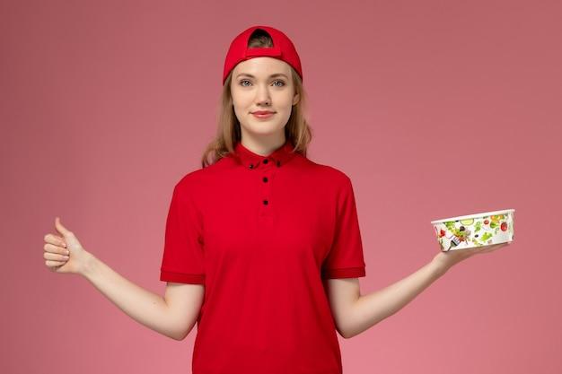 Vue de face femme courrier en uniforme rouge et cape tenant le bol de livraison sur le mur rose clair, prestation uniforme de travailleur de service emploi