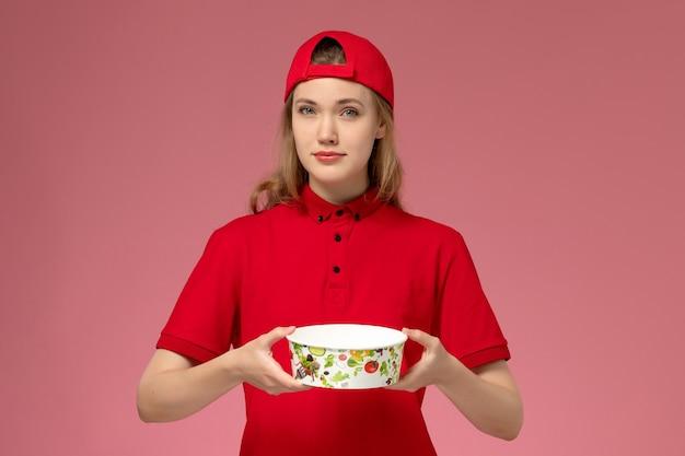 Vue de face femme courrier en uniforme rouge et cape tenant le bol de livraison sur le mur rose clair, travail de livraison uniforme de service
