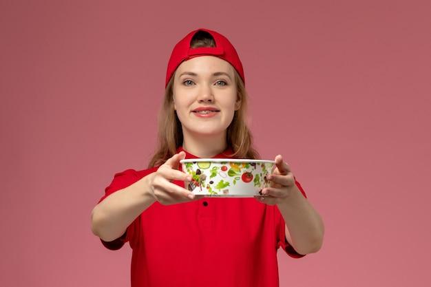 Vue de face femme courrier en uniforme rouge et cape tenant le bol de livraison sur le mur rose clair, travail travail fille service livraison uniforme