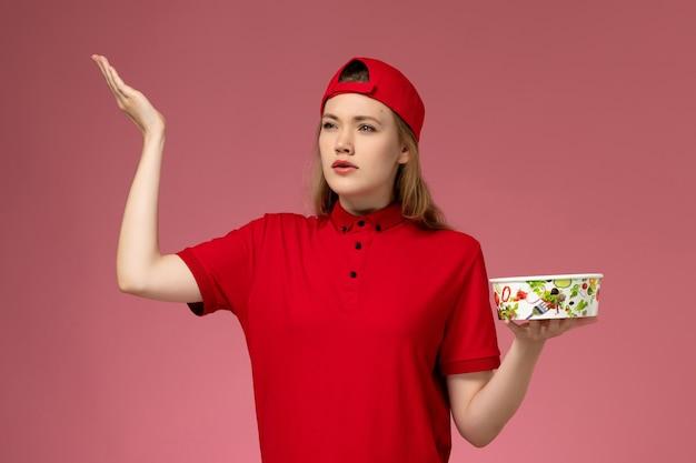 Vue de face femme courrier en uniforme rouge et cape tenant le bol de livraison sur le mur rose clair, travail de travail de travailleur de livraison uniforme de service