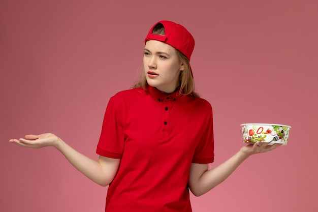 Vue de face femme courrier en uniforme rouge et cape tenant le bol de livraison sur le mur rose clair, travail travailleur travail fille service livraison uniforme