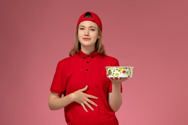 Vue de face femme courrier en uniforme rouge et cape tenant le bol de livraison sur le mur rose clair, travailleur de livraison uniforme de service d'emploi
