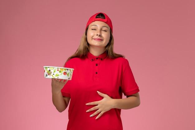 Vue de face femme courrier en uniforme rouge et cape tenant le bol de livraison sur le mur rose, service de livraison de travailleur uniforme