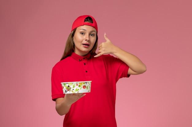 Vue de face femme courrier en uniforme rouge et cape tenant le bol de livraison sur le mur rose, travail de service de livraison uniforme