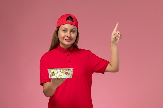 Vue de face femme courrier en uniforme rouge et cape tenant le bol de livraison sur le mur rose, travailleur de l'emploi de service de livraison uniforme