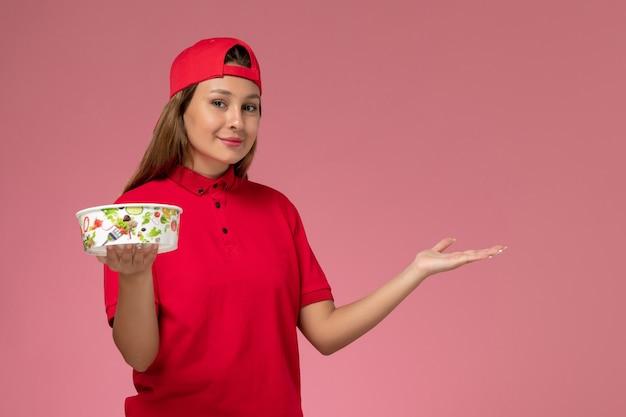Vue de face femme courrier en uniforme rouge et cape tenant le bol de livraison sur le mur rose, travailleur de service de livraison uniforme