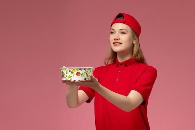 Vue de face femme courrier en uniforme rouge et cape tenant le bol de livraison et souriant sur mur rose clair, service de livraison uniforme