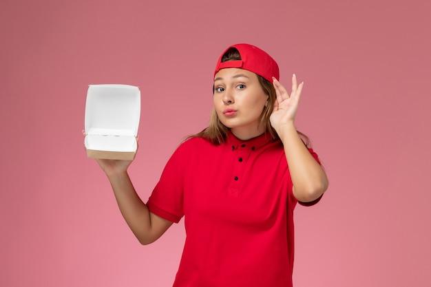 Vue de face femme courrier en uniforme rouge et cape tenant un colis alimentaire de livraison vide et essayant d'entendre sur un mur rose clair, entreprise de service de livraison uniforme
