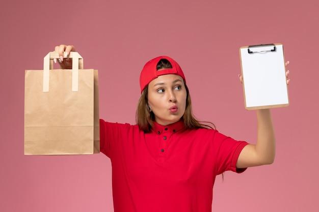 Vue de face femme courrier en uniforme rouge et cape tenant le paquet de nourriture de livraison avec bloc-notes sur mur rose clair, service de travail de livraison uniforme