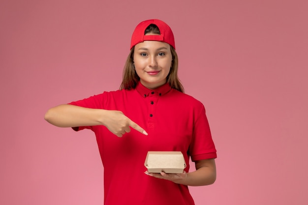 Vue de face femme courrier en uniforme rouge et cape tenant le paquet de nourriture de livraison sur fond rose clair service de livraison uniforme entreprise emploi