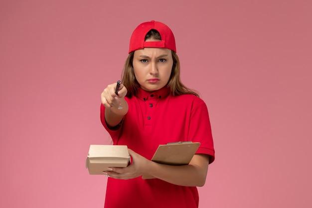 Vue de face femme courrier en uniforme rouge et cape tenant peu de colis alimentaires de livraison et bloc-notes d'écriture de notes sur le mur rose, service de livraison uniforme