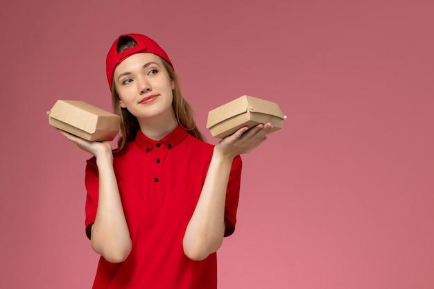 Vue de face femme courrier en uniforme rouge et cape tenant peu de colis alimentaires de livraison sur le mur rose, fille uniforme de l'entreprise de services de livraison