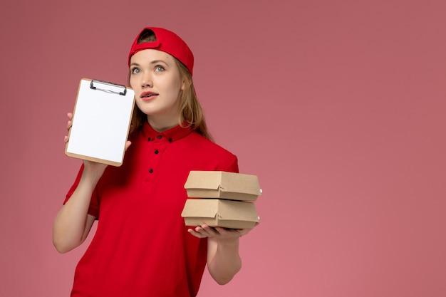 Vue de face femme courrier en uniforme rouge et cape tenant peu de colis alimentaires de livraison pensant sur mur rose clair, service de livraison uniforme