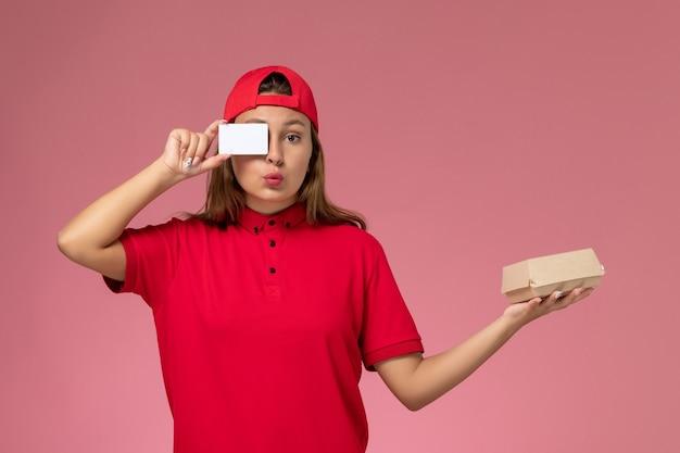 Vue de face femme courrier en uniforme rouge et cape tenant peu de colis de nourriture de livraison et carte sur mur rose clair, travail de service de livraison uniforme de travailleur