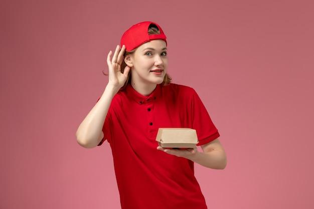 Vue de face femme courrier en uniforme rouge et cape tenant peu de colis de nourriture de livraison et essayant d'entendre sur le mur rose, travail uniforme de l'entreprise de service de livraison