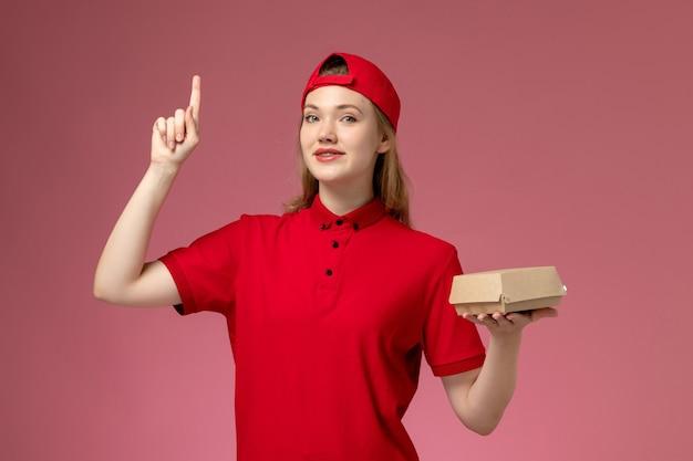 Vue de face femme courrier en uniforme rouge et cape tenant peu de colis de nourriture de livraison sur le mur rose clair, travail uniforme de l'entreprise de services de livraison