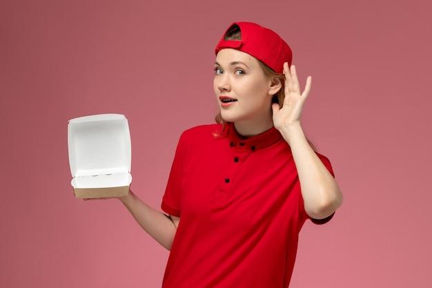Vue de face femme courrier en uniforme rouge et cape tenant peu de colis de nourriture de livraison vide essayant d'entendre sur le mur rose, service de livraison emploi uniforme