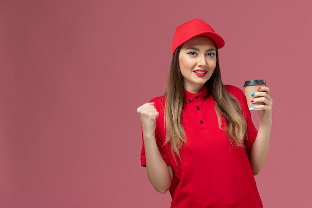 Vue de face femme courrier en uniforme rouge et cape tenant la tasse de café de livraison et se réjouir sur le fond rose service de livraison de travail uniforme travailleur