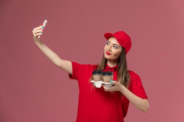 Vue de face femme courrier en uniforme rouge tenant des tasses de café de livraison en prenant des photos avec eux sur fond rose uniforme de livraison de service d'emploi de travailleur