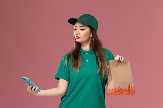 Vue de face femme courrier en uniforme vert à l'aide de téléphone et tenant un paquet de nourriture sur le mur rose service de livraison uniforme de travail