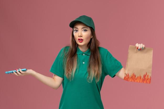 Vue de face femme courrier en uniforme vert à l'aide de téléphone et tenant le paquet de nourriture sur le mur rose service de livraison uniforme travailleur