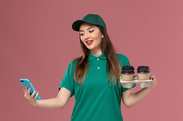 Vue de face femme courrier en uniforme vert et cape à l'aide de téléphone et tenant des tasses de café de livraison sur le mur rose service de livraison uniforme de travail