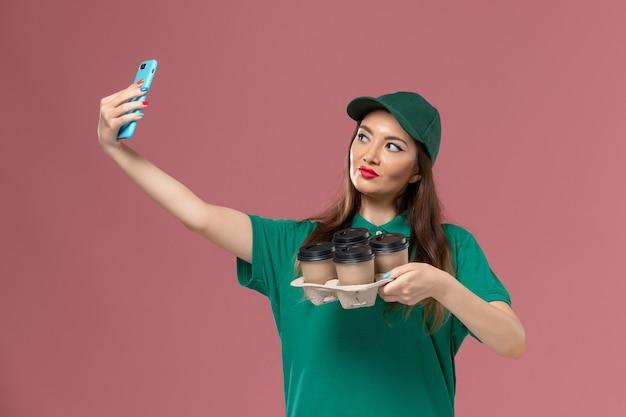 Vue de face femme courrier en uniforme vert et cape prenant des photos avec des tasses de café de livraison sur le mur rose service de livraison uniforme dame travail