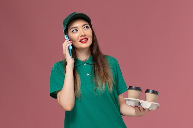 Vue de face femme courrier en uniforme vert et cape tenant des tasses de café de livraison parler au téléphone sur la livraison uniforme de service de bureau rose