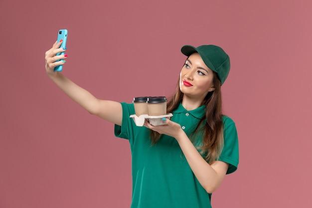 Vue de face femme courrier en uniforme vert et cape tenant des tasses de café de livraison en prenant photo sur le mur rose service de livraison uniforme de travail