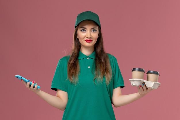 Vue de face femme courrier en uniforme vert et cape tenant des tasses de café de livraison et son téléphone sur la livraison uniforme de travail de bureau rose