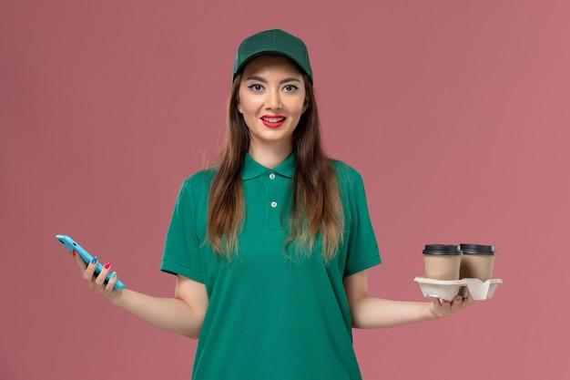 Vue de face femme courrier en uniforme vert et cape tenant des tasses de café de livraison et téléphone sur la livraison uniforme de service de mur rose