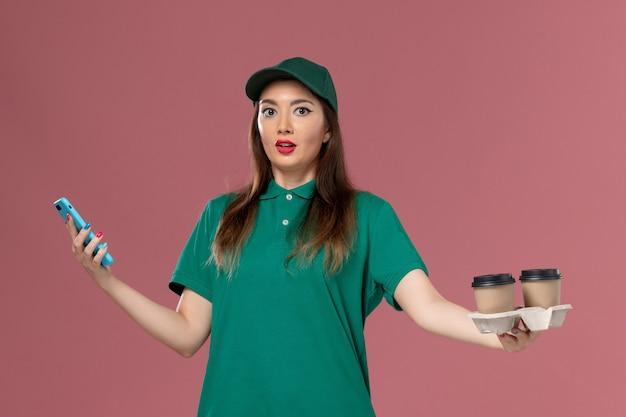 Vue de face femme courrier en uniforme vert et cape tenant des tasses de café de livraison et téléphone sur la livraison uniforme de travail de bureau rose