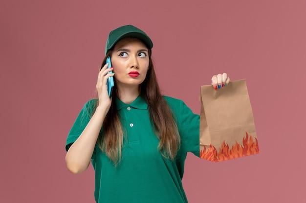 Vue de face femme courrier en uniforme vert parler au téléphone et tenant le paquet de nourriture sur le mur rose service de livraison uniforme de travail