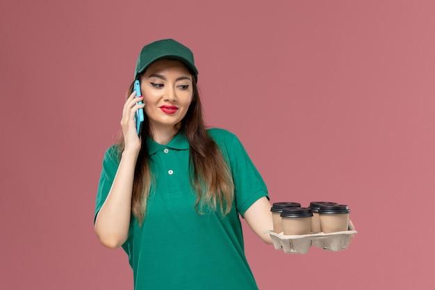 Vue de face femme courrier en uniforme vert parler au téléphone et tenant des tasses de café de livraison sur le service de plancher rose travail de livraison uniforme
