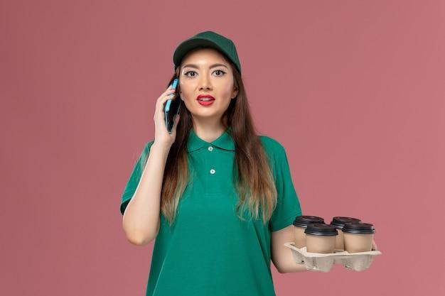 Vue de face femme courrier en uniforme vert parler au téléphone et tenant des tasses de café de livraison sur le travail de livraison uniforme de service de bureau rose
