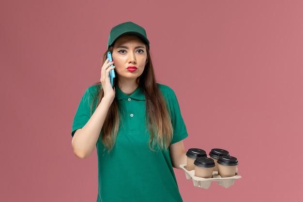 Vue de face femme courrier en uniforme vert parler au téléphone et tenant des tasses de café de livraison sur le travail de livraison uniforme de travailleur de service de mur rose