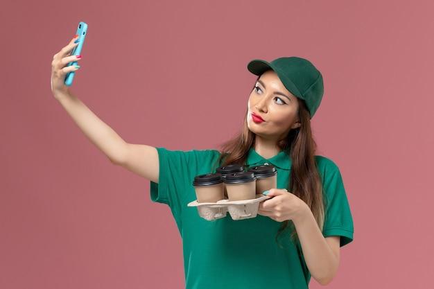 Vue de face femme courrier en uniforme vert prendre une photo avec des tasses de café de livraison sur le mur rose service de livraison uniforme