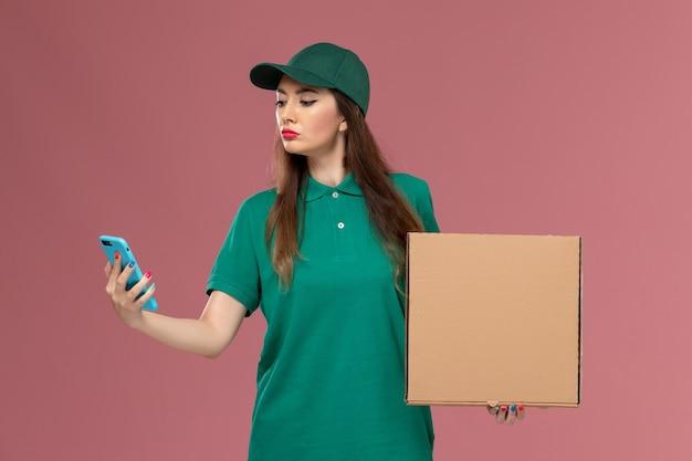 Vue de face femme courrier en uniforme vert tenant la boîte de livraison de nourriture et à l'aide de son téléphone sur le mur rose clair service de l'entreprise de travail de livraison uniforme
