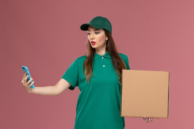 Vue de face femme courrier en uniforme vert tenant la boîte de livraison de nourriture et à l'aide de son téléphone sur le mur rose service de l'entreprise de livraison d'uniforme