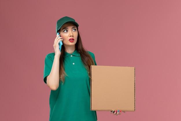 Vue de face femme courrier en uniforme vert tenant la boîte de livraison de nourriture à l'aide de son téléphone sur le mur rose service de l'entreprise de travail de livraison uniforme