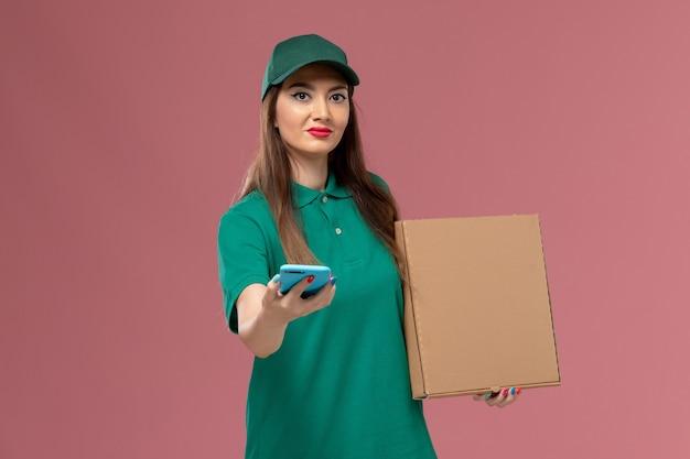 Vue de face femme courrier en uniforme vert tenant la boîte de livraison de nourriture à l'aide de téléphone sur le mur rose service de livraison uniforme de travail