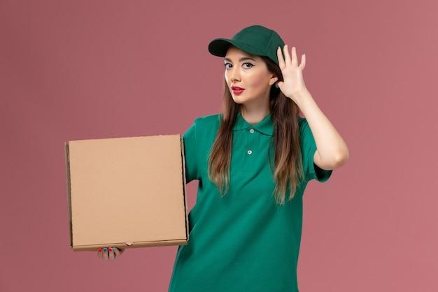 Vue de face femme courrier en uniforme vert tenant boîte de nourriture essayant d'entendre sur le mur rose travail de livraison uniforme de service d'emploi